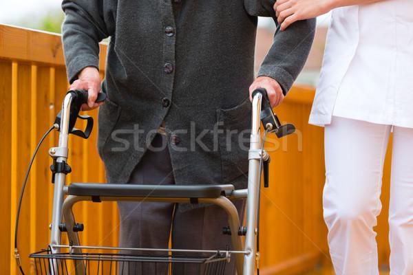 Young nurse and female senior with walking frame Stock photo © Kzenon