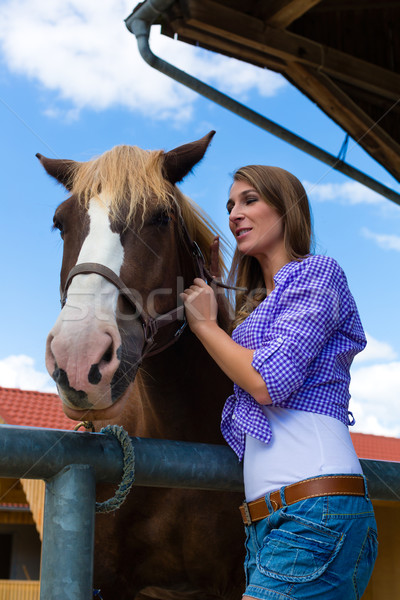 Young woman in the stable with horse in sunshine Stock photo © Kzenon