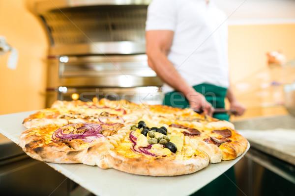 Man voortvarend afgewerkt pizza oven schop Stockfoto © Kzenon