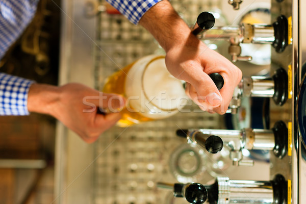 Man drawing beer from tap Stock photo © Kzenon