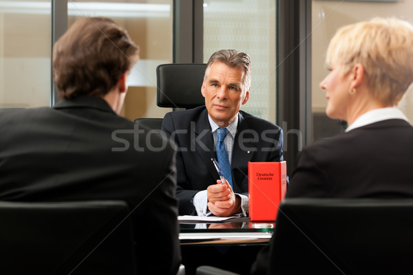 Lawyer or notary with clients in his office Stock photo © Kzenon