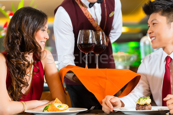 Stock photo: Waiter serving Chinese couple wine in fancy restaurant