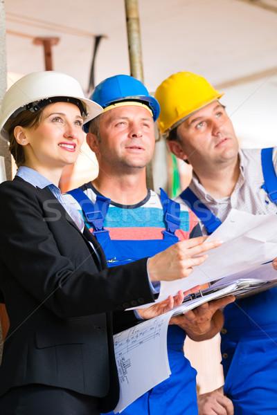 Stock photo: Work Team on construction site controlling floor plan