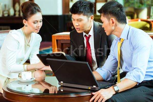 Kínai üzletemberek megbeszélés hotel lobbi három Stock fotó © Kzenon