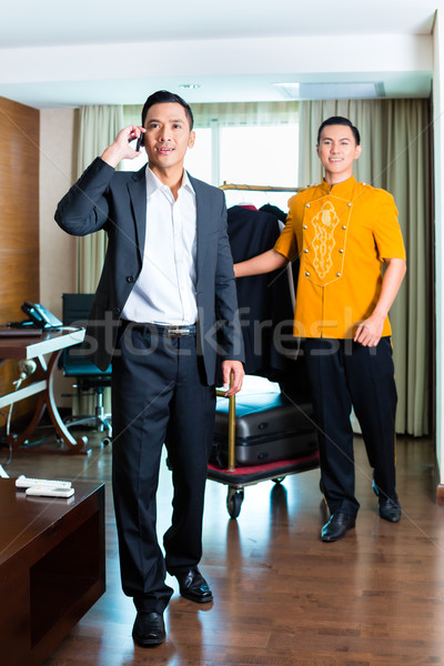 Guest and bell boy standing in hotel room Stock photo © Kzenon