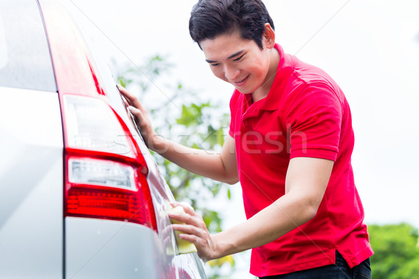Asian man cleaning and washing car with sponge Stock photo © Kzenon