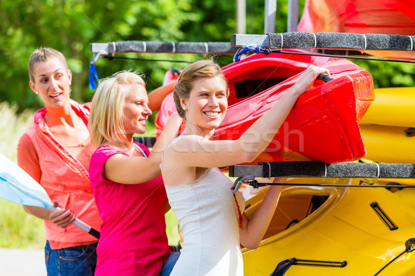 Three women unloading kayak from boat trailer Stock photo © Kzenon