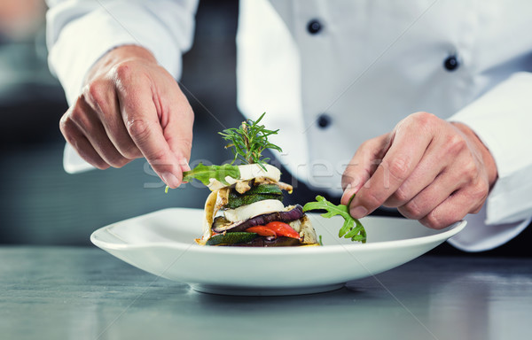 Chef in Restaurant garnishing vegetable dish Stock photo © Kzenon