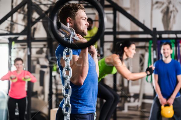 Man lifting dumbbell in functional training gym session Stock photo © Kzenon