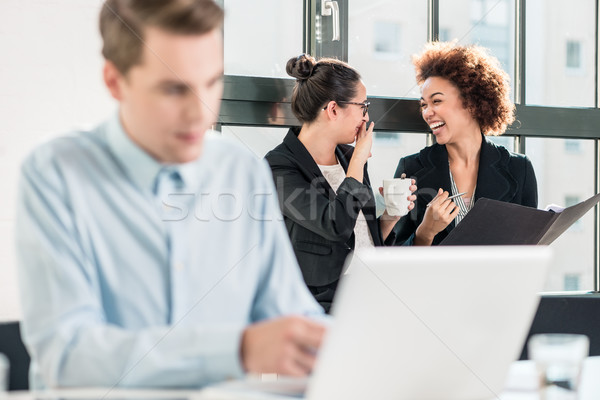 Two young women laughing behind their male colleague Stock photo © Kzenon