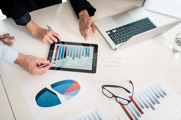 Professional team analyzing bar chart displayed on tablet PC Stock photo © Kzenon