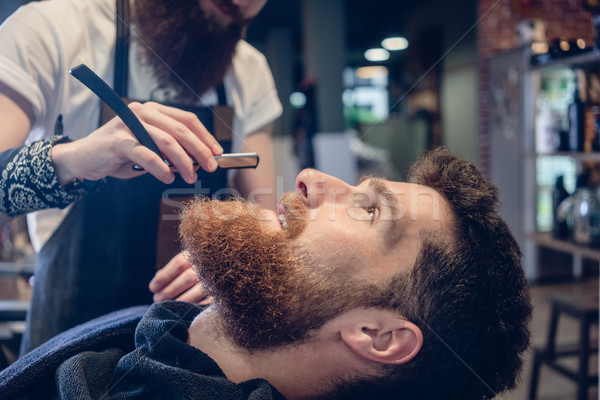 Bearded young man ready for shaving in the hair salon of a skill Stock photo © Kzenon
