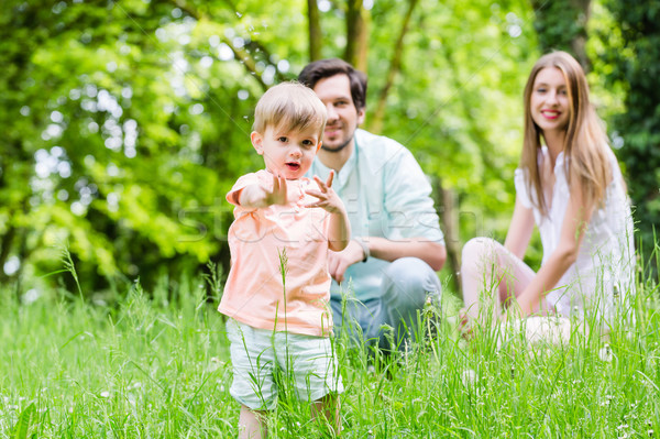 Little boy running over meadow with family in back Stock photo © Kzenon