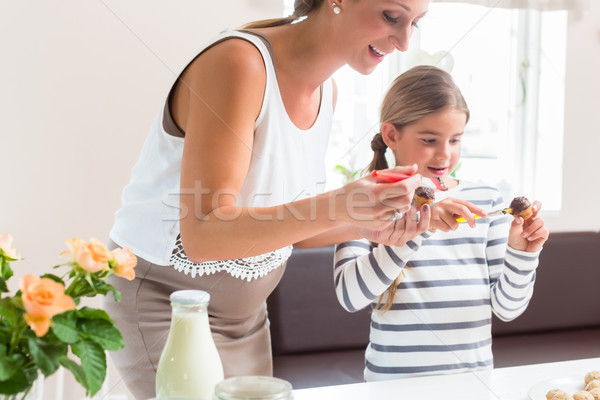 Pregnant mother baking cupcakes with her daughter Stock photo © Kzenon