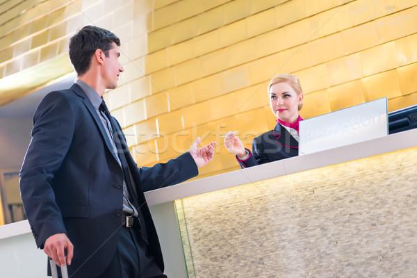 Man on business trip at hotel reception Stock photo © Kzenon