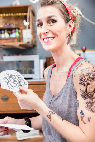 Portrait of a fashionable woman happy for choosing two roses for her new tattoo Stock photo © Kzenon