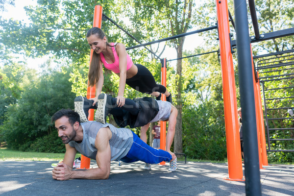 Three friends forming a pyramid while doing push-up and plank exercises Stock photo © Kzenon