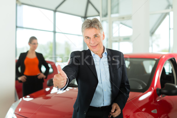 Mature man with woman and auto in car dealership Stock photo © Kzenon
