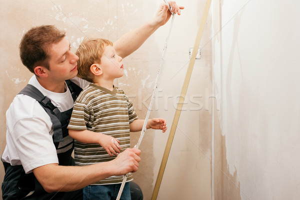 Father and son measuring dry wall Stock photo © Kzenon