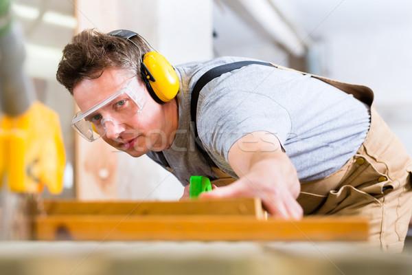 Carpenter using electric saw in carpentry Stock photo © Kzenon