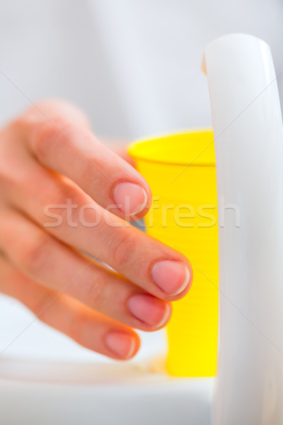 Patient rinse mouth with a cup of water at dentist Stock photo © Kzenon