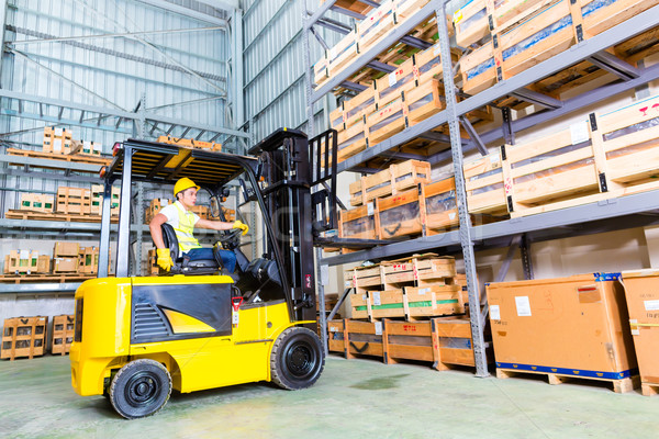 Asian fork lift truck driver lifting pallet in storage Stock photo © Kzenon
