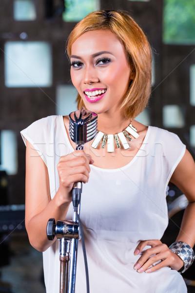 Asian singer producing song in recording studio Stock photo © Kzenon