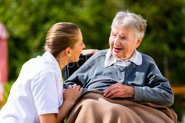 Stock photo: Nurse holding hands with senior woman in wheelchair