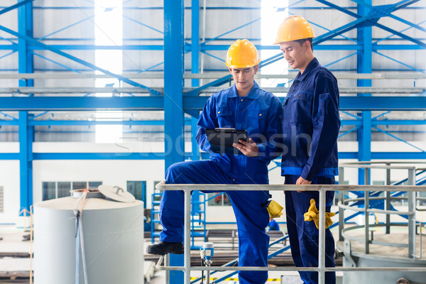 Workers in large metal workshop checking work Stock photo © Kzenon