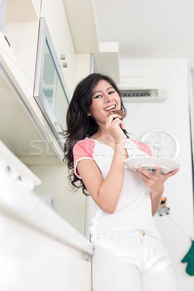 Indonezyjski kobieta jedzenie cookie kuchnia Zdjęcia stock © Kzenon