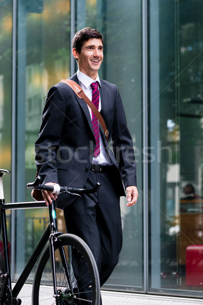 Businessman walking in town wheeling a bicycle Stock photo © Kzenon
