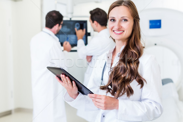 Doctor with colleagues standing in hospital at CT machine with s Stock photo © Kzenon