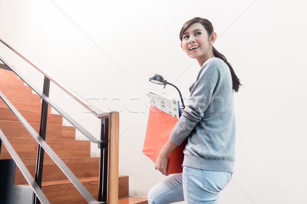 Young Indonesian girl carrying removal crate up the stairs Stock photo © Kzenon