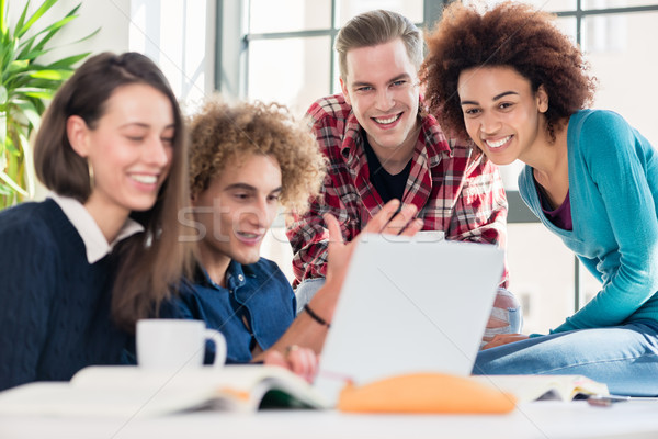 Students watching together a funny online video on a laptop duri Stock photo © Kzenon
