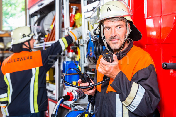 Chief fire fighter  checking radio set Stock photo © Kzenon