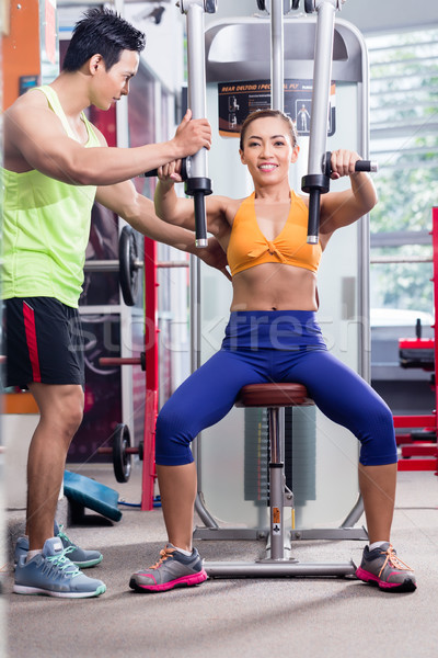 Instructor supervising sportive woman during workout Stock photo © Kzenon