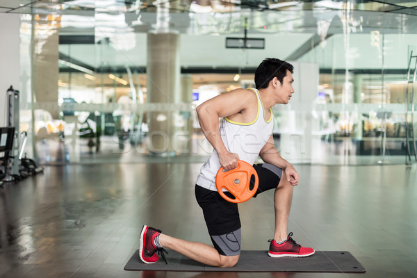Fit young man exercising with a weight plate during upper-body workout Stock photo © Kzenon