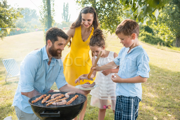 Dedicated father helping son to use wooden tongs during family picnic Stock photo © Kzenon