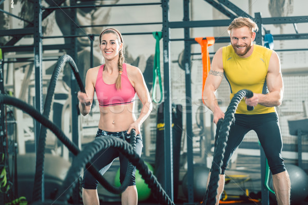 Strong couple exercising together with battle ropes during functional training Stock photo © Kzenon