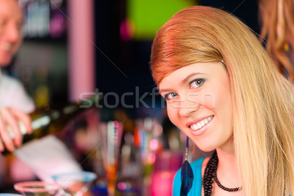 Young woman in club or bar drinking champagne Stock photo © Kzenon