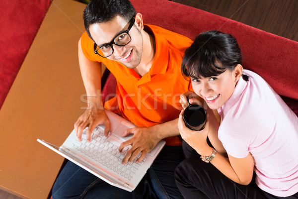 Asian couple on the couch with a laptop Stock photo © Kzenon