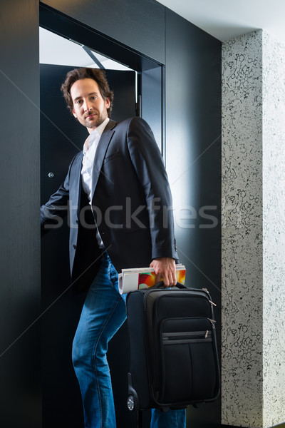 Young guest with luggage entering hotel room Stock photo © Kzenon