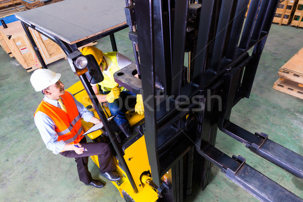 Asian lift truck driver and foreman in storage Stock photo © Kzenon