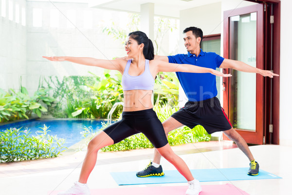 Asian fitness couple at sport workout in tropical home Stock photo © Kzenon