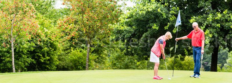 Senior woman and man playing golf putting on green Stock photo © Kzenon