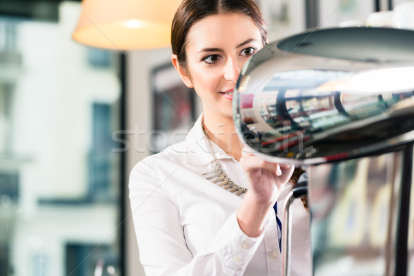 Young waitress preparing coffee in a modern location Stock photo © Kzenon