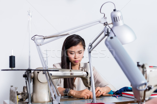 Woman using sewing machine, addition of buttons, red fabric, fixing pins  Stock photo © Kzenon