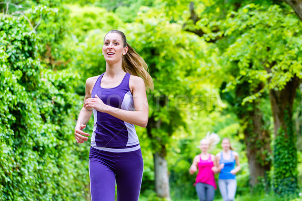 fast jogger in forest outpacing two friends Stock photo © Kzenon