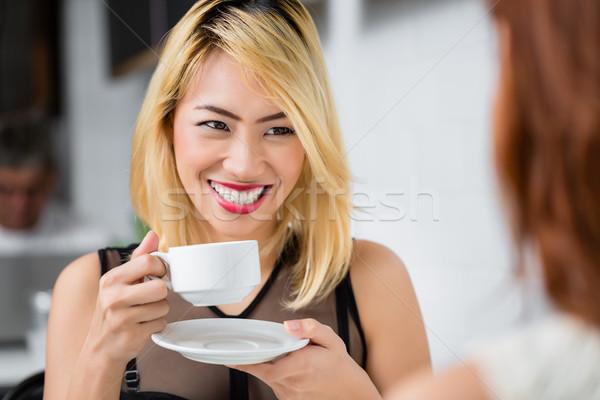 Beautiful blond Asian woman drinking coffee Stock photo © Kzenon