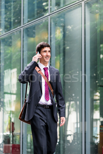 Happy young man wearing business suit while talking on mobile ph Stock photo © Kzenon